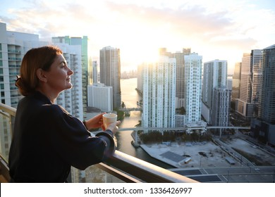 woman in bathrobe drinking Her morning coffee or tea on a downtown balcony. beautiful sunrise in downtown Miami. Woman enjoying Miami downtown city view from a balcony. rent to own