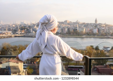 Woman in bathrobe on the terrace of a house at sunrise
