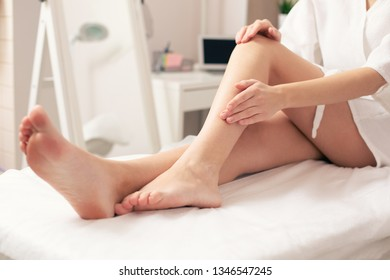 Woman in bathrobe sitting on the medical couch and touching her leg