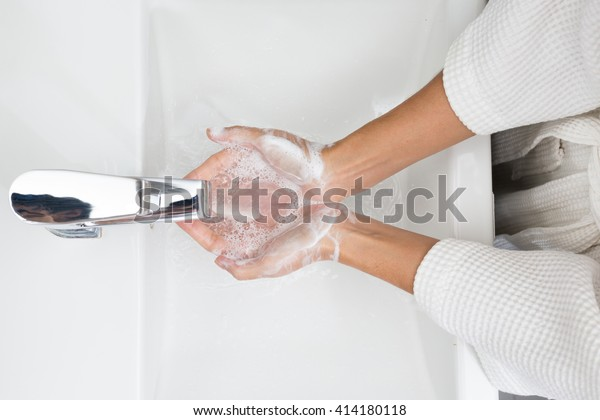 Woman in a bathrobe is washing hands.
