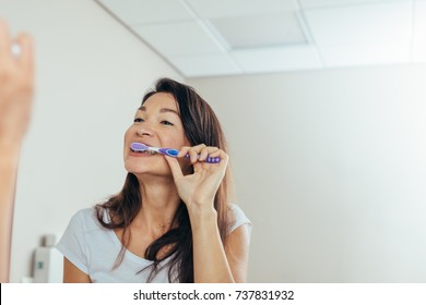 Woman in the bathroom brushing teeth. Reflection of asian woman in bathroom mirror while brushing teeth in morning.