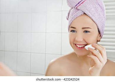 Woman at the bathroom with cotton pad applying