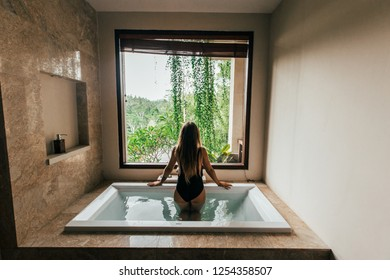 Woman in bathroom with window. Great view on the tropic forest and jungle from window in bathroom