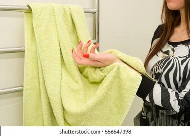 Woman in bathroom is wiping her hands using green towel