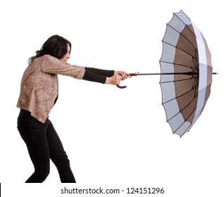 Woman battling with her umbrella in wind desperately holding on to the handle as the force of the gale tries to rip it from her hands isolated on white