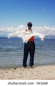 A woman at the beach feeling the wind through her clothes.