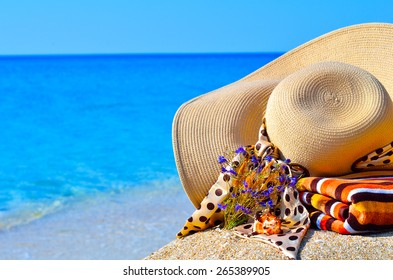 Woman beach hat, bright towel and flowers against blue ocean background