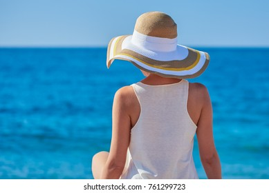 Woman in beach hat looking at the sea.