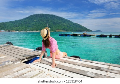 Woman at beach jetty wearing hat