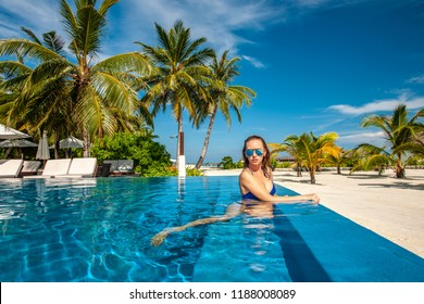 Woman at beach swimming pool in Maldives