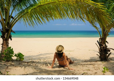 Woman at beach under palm tree with leaf shadow on her body