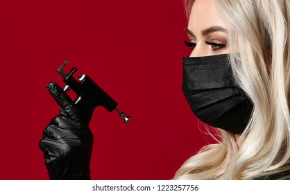 Woman beautician cosmetologist hold new popular ear piercing gun in black medical gloves and mask on red background