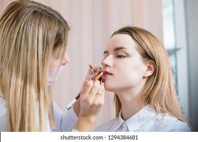 Woman beautician prepares the patient, a young woman, for permanent makeup lips, drawing the boundaries of a pencil in the office