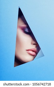 Woman with a beautiful bright makeup and pink lipstick looks through a triangular hole in the blue paper. Advertising cosmetics, professional art makeup, lip gloss, bright color, blue background
