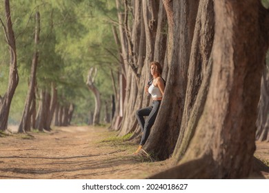 A woman in beautiful dress walking in the pine tree tunnel. Tree Tunnel beside the beach. Large pine trees line up to form a tunnel background.