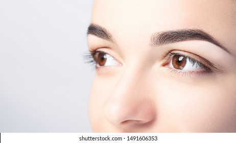 Woman with beautiful eyebrows close-up on a light background with copy space. Microblading, microshading, eyebrow tattoo, henna, powder brows concept.