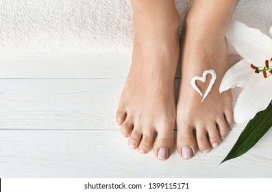Woman with beautiful feet, cream, flower and towel on white wooden floor, closeup. Spa treatment