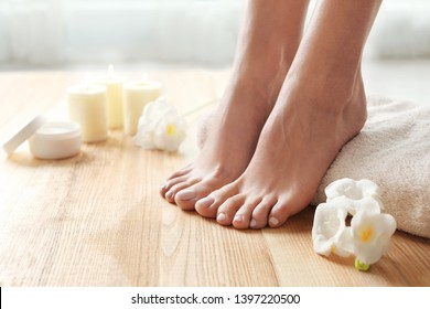 Woman with beautiful feet, towel and flowers on wooden floor, closeup. Spa treatment