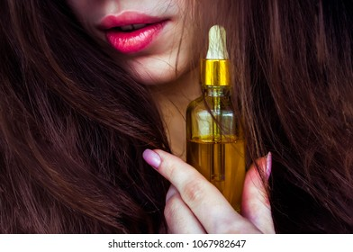 a woman with beautiful hair holds hair oil. The concept of hair care