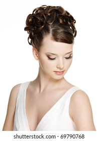 Woman with beautiful hairstyle and brown make-up using long false eyelash, on white background