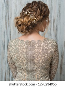 Woman with beautiful hairstyle decorated by gold shiny hair accessory, rear view