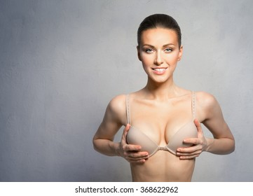 Woman with beautiful, large breasts, happy after plastic surgery.