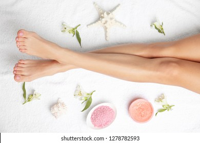 Woman with beautiful legs, cosmetic and flowers on white towel, top view. Spa treatment