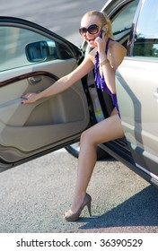 woman with beautiful legs exit the car and talking on mobile phone