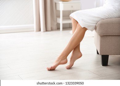 Woman with beautiful legs and feet sitting on ottoman indoors, closeup with space for text. Spa treatment
