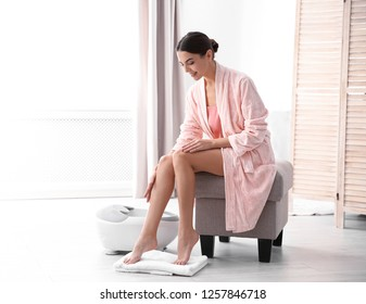 Woman with beautiful legs sitting near foot bath at home, space for text. Spa treatment