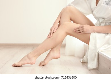Woman with beautiful legs sitting on window sill in room