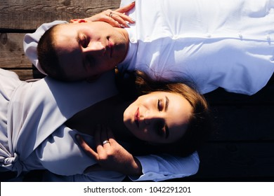 A woman with a beautiful makeup and her husband lie on a wooden surface and closed their eyes