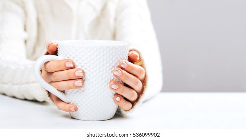 Woman with beautiful manicure holding big white cup of hot coffee. Place for text.