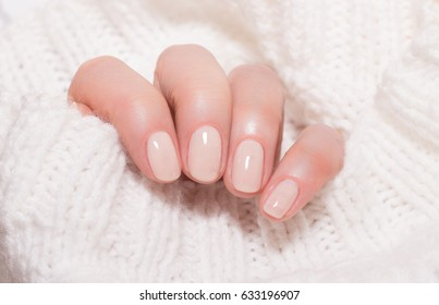 Woman with beautiful manicured beige fingernails gracefully crossing her hands to display them to the viewer on a red background in a fashion, glamour and beauty concept