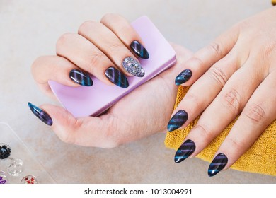 Woman with beautiful manicured fashion nails holding nail file, top view, copy space