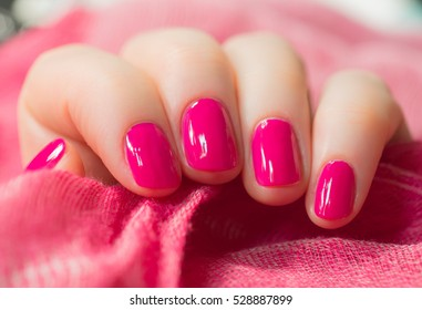 Woman with beautiful manicured pink fingernails gracefully crossing her hands to display them to the viewer on a white background in a fashion, glamour and beauty concept