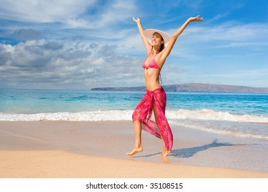 woman with beautiful pink sarong on tropical beach happy in maui, hawaii