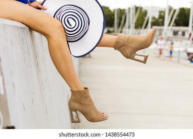 Woman beautiful slim legs wearing suede beige high heels shoes holding sun hat