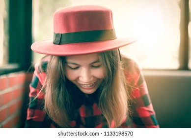 woman with beautiful smile reading message  on mobile phone during rest in coffee shop