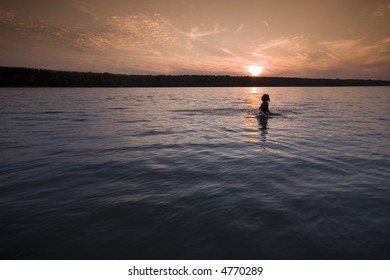 Woman and a beautiful sunset on the river