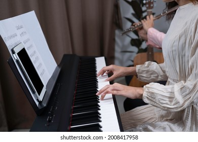 A woman in beautiful white dress press key on paino, tablet and key note put on paino holder, her friend playing flute beside with blurred guitar and home. Playing music together at home for fun.
