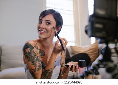 Woman beauty blogger recording a video tutorial on camera showing how to apply make up. Female vlogger recording a makeup vlog for her online channel.