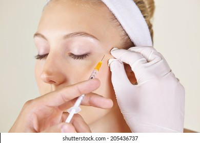 Woman in beauty clinic getting wrinkles treatment near her ayes ageinst crow's feet