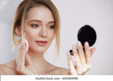 Woman Beauty Face. Closeup Of Beautiful Female With Cushion Puff And Mirror Applying Makeup Powder Foundation. Portrait Of Sexy Girl With Fresh Soft Skin Putting Cosmetic Product. High Resolution
