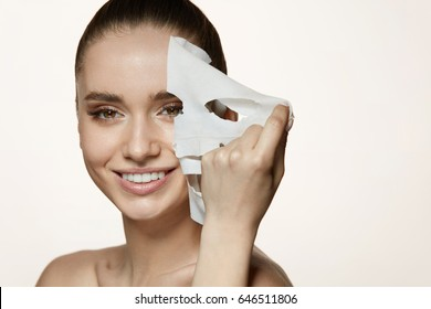 Woman Beauty Face. Closeup Of Smiling Young Female With Fresh Natural Makeup Removing Textile Sheet Mask From Facial Skin. Portrait Of Attractive Happy Girl With White Cosmetic Mask. High Resolution