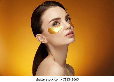Woman Beauty Face With Mask Under Eyes. Closeup Of Beautiful Smiling Girl With Gold Patches, Golden Collagen Mask On Facial Skin. High Resolution
