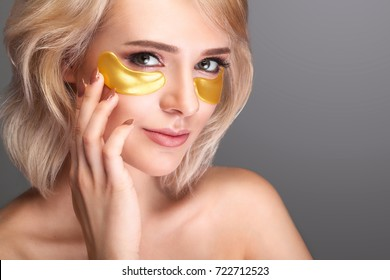 Woman Beauty Face With Mask Under Eyes. Beautiful Female With Natural Makeup And Gold Collagen Patches On Fresh Facial Skin. High Resolution