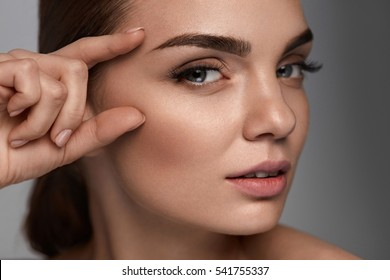 Woman Beauty Face. Portrait Of Beautiful Young Woman With Professional Makeup And Perfect Smooth Healthy Skin. Sexy Female Model With Fingers Near Face On Grey Background. Skin Care. High Resolution