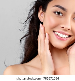 Woman beauty face portrait isolated on gray with healthy skin and white teeth smile. Studio shot.