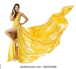 Woman Beauty Fashion Dress, Beautiful Girl In Flying Yellow Fluttering Gown, Standing on One Leg High Heels, Surprised with Open Mouth. Fabric Cloth Waving on Wind, Isolated Over White Background
